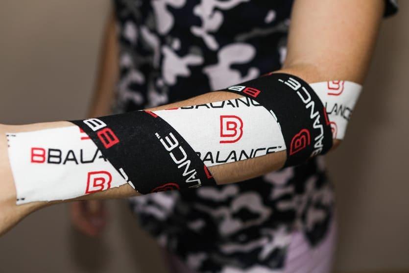 Белые и черные кинезио тейпы BBTape на клеяны на руку девушки при процедуре кинезиотейпирования руки.